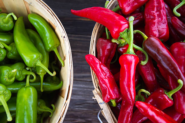 red and green chile peppers in bushel baskets - green chilli pepper stock photos and pictures