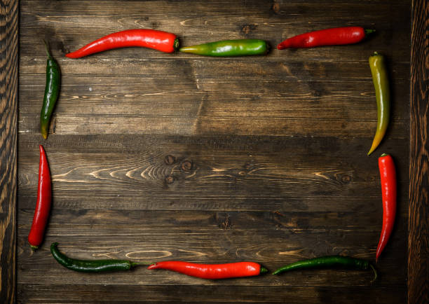 red and green chili pepper on plate on wooden background - green chilli pepper stock photos and pictures