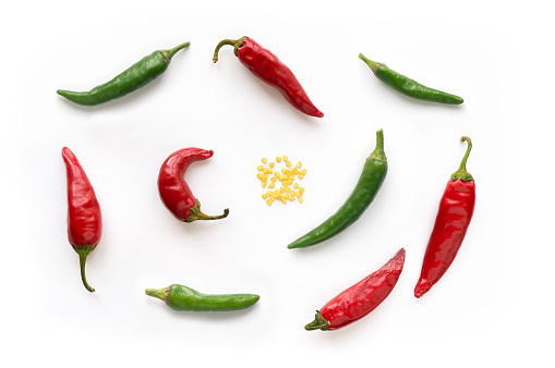Isolated chili peppers with seeds on white background. Top view.