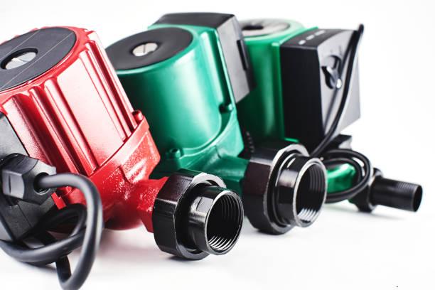 Rote und grüne Umwälzpumpen für die Heizung auf einem weißen Hintergrund. – Foto