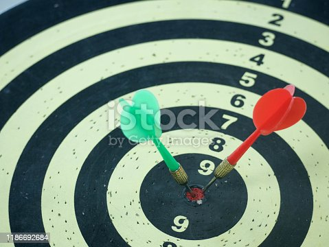 istock Red and Green dart target arrow hitting on bullseye which is the ultimate goal that everyone wants, Target marketing and business success concept 1186692684