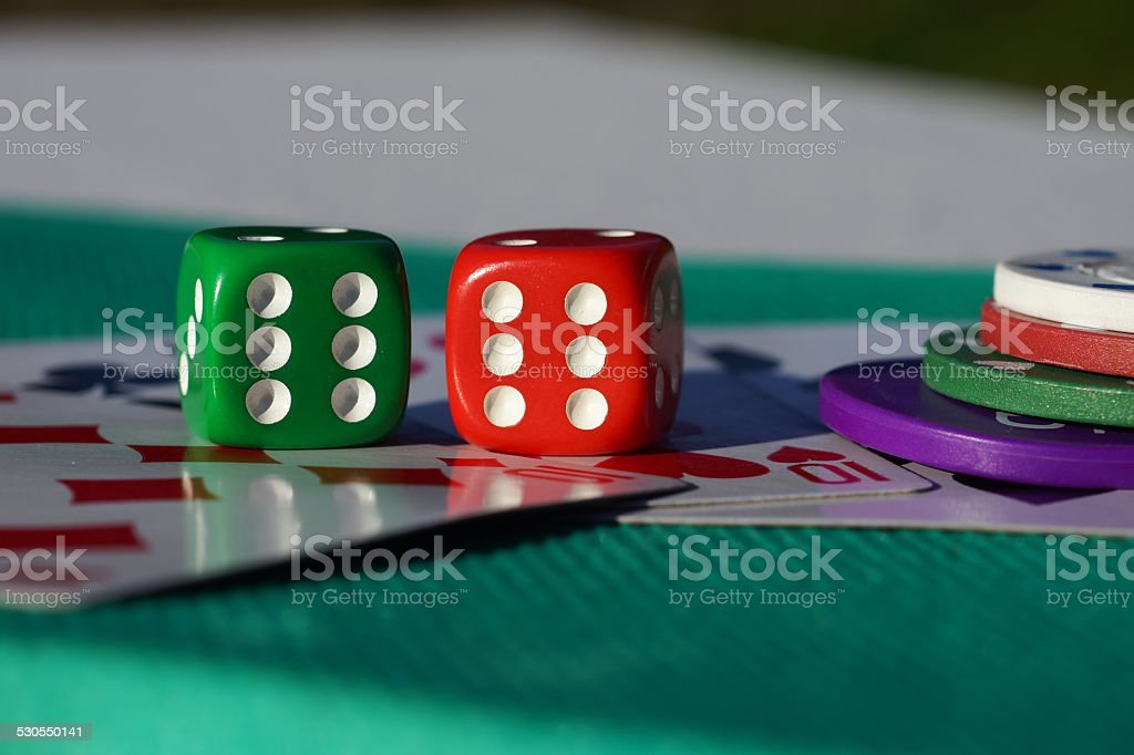 Red and green dice on a pile of cards stock photo