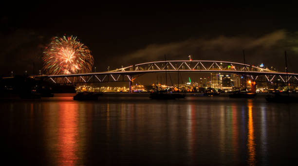 Red and green fireworks for New Year celebration with Auckland Harbor Bridge illuminated Red and green fireworks for New Year celebration with Auckland Harbor Bridge illuminated dazzled stock pictures, royalty-free photos & images