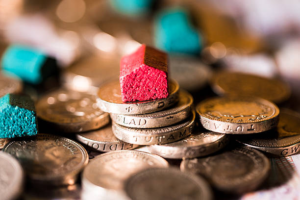 Red and Green Houses on top of Piles of Coins Macro close up image of wooden houses on top of piles of British pound coins, illustrating a mortgage, housing and savings concept. Horizontal colour image with extremely shallow depth of field. Room for copy space borrowing stock pictures, royalty-free photos & images