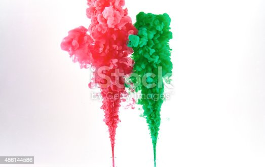 istock Red and green ink making clouds in water 486144586
