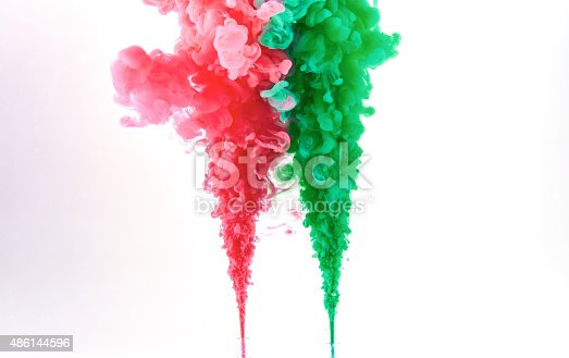 istock Red and green ink making clouds in water 486144596