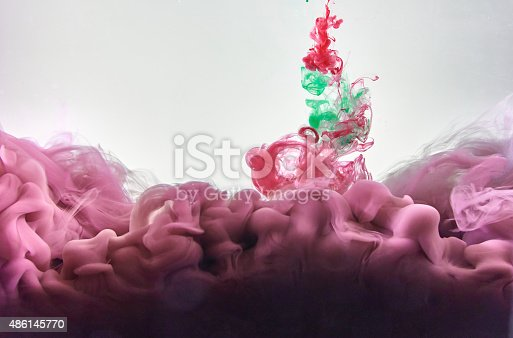 istock Red and green ink making clouds in water 486145770