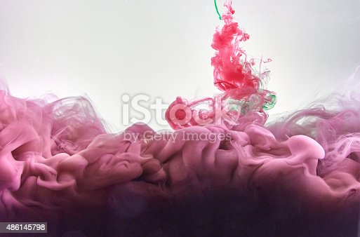 istock Red and green ink making clouds in water 486145798