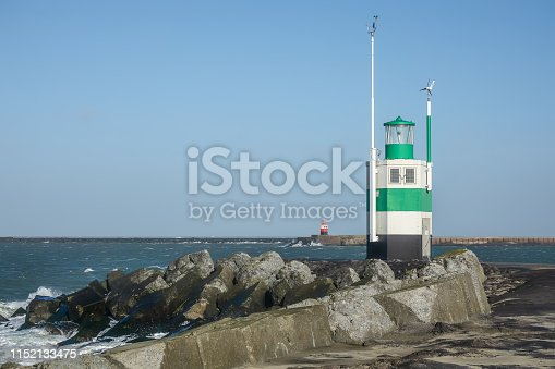 615497916 istock photo Red and green light house at the shore of IJmuiden in the Netherlands. The lighthouses are intended as a beacon for shipping 1152133475