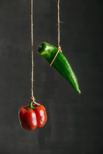 Red and green peppers suspended on a string against black background stock photo
