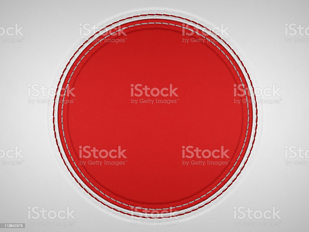 Red and grey stitched circle shape on leather royalty-free stock photo