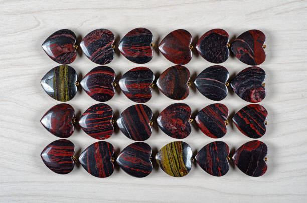 Red and iron tiger eye heart-shaped stones as background stock photo