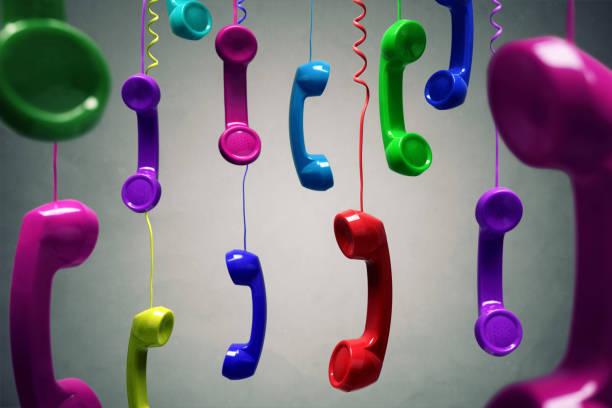 red and multi-coloured telephone receiver hanging - cornetta telefono foto e immagini stock