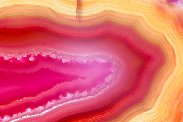 Red and orange agate slice mineral with parallel and curved lines, abstract background stock photo