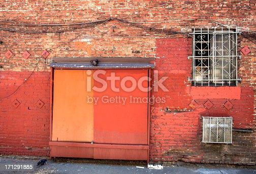 Red and orange dominate the rear of a brick building with security-barred windows, cables, and loading dock door. Horizontal.