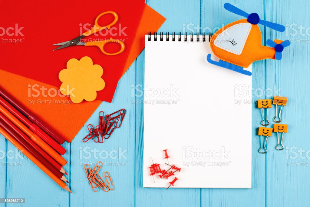 Red and orange pencils, felt-tip pens, notepaper, paper clips, stationery nails, felt and scissors on blue wooden background stock photo