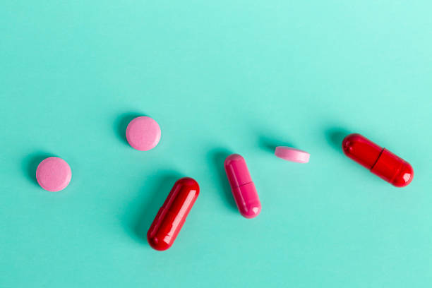 Red and pink medicinal tablets and capsules stock photo