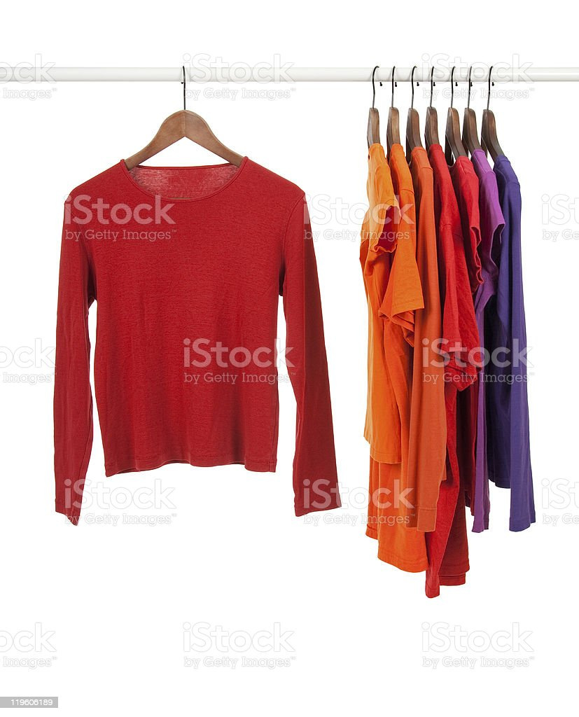 Red and purple shirts on wooden hangers stock photo