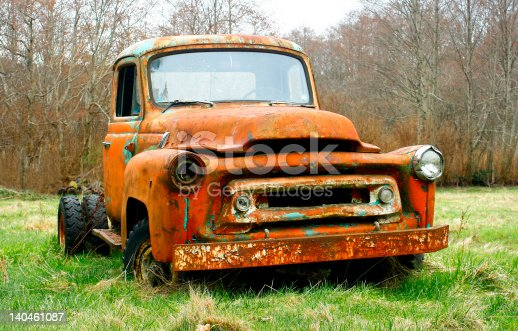 Red and rusty truck in country field.