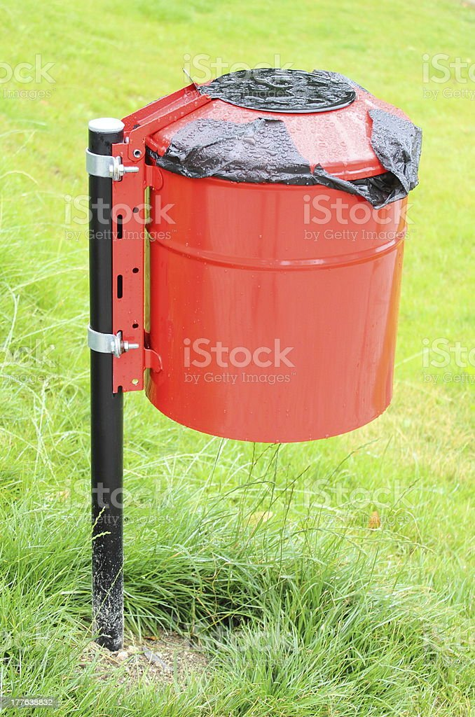 Red and wet garbage basket in a park royalty-free stock photo