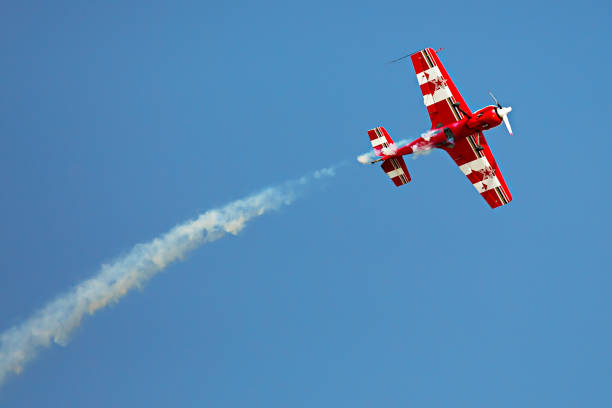 red and white airplane with the trace of white smoke behind it in the sky in the airshow - airshow stock photos and pictures