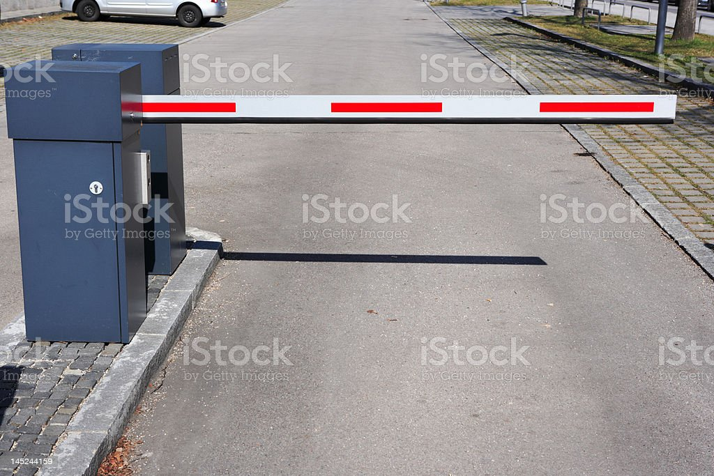 red and white barrier at parking lot entrance stock photo