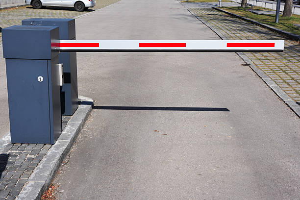 red and white barrier at parking lot entrance red and white barrier at parking lot entrance security barrier stock pictures, royalty-free photos & images