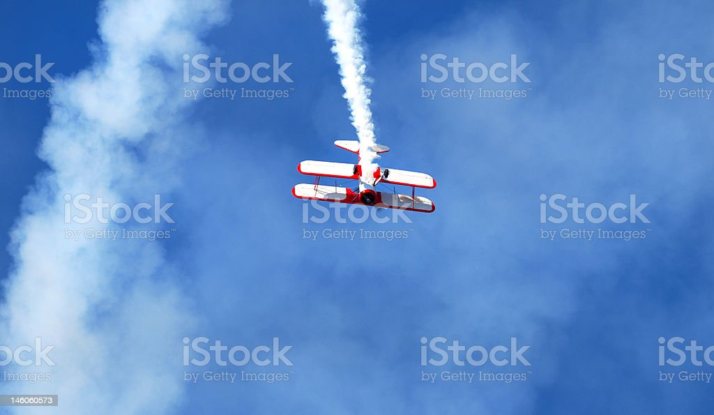 Red and white biplane doing stunts at air show royalty-free stock photo