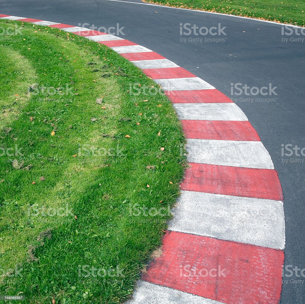 Red and white border and lawn interior of a paved racetrack royalty-free stock photo