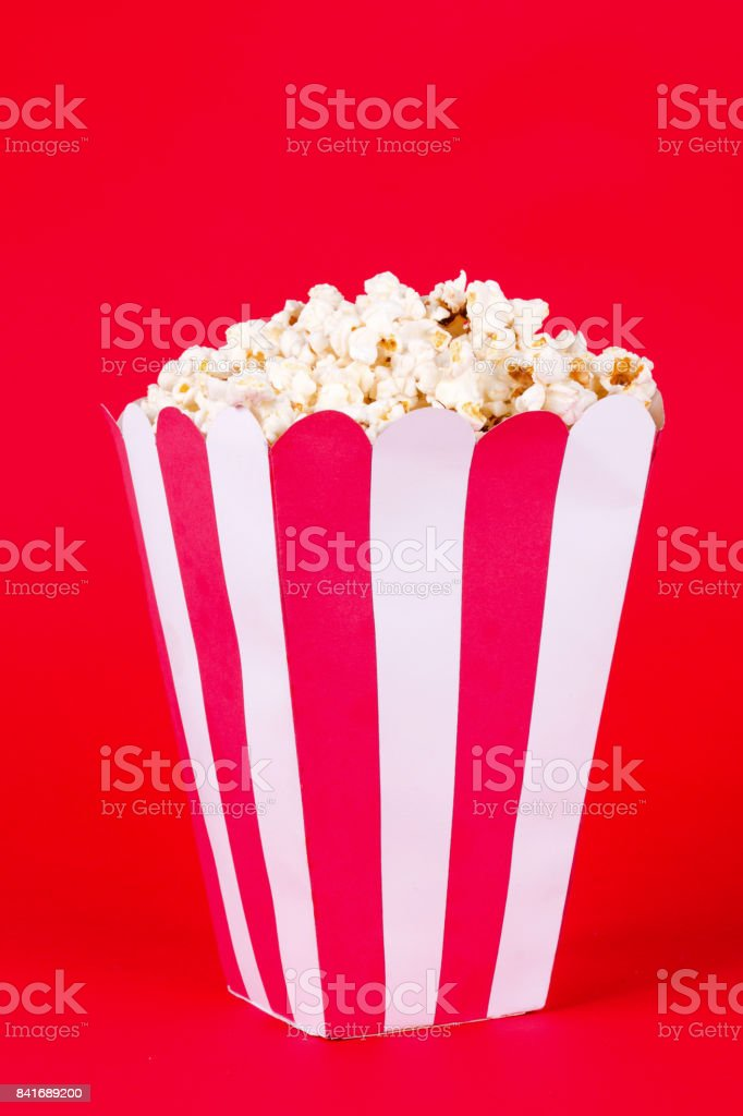 Red and white box with popcorn isolated on red backgroun. Food and...