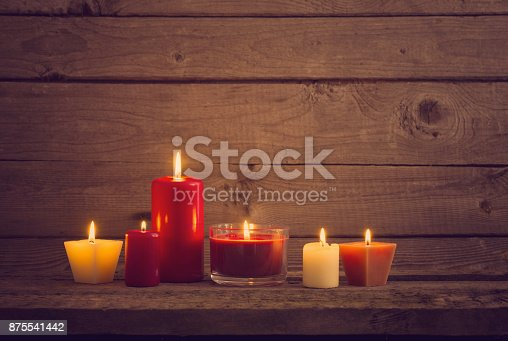 istock red and white candles on dark wooden background 875541442