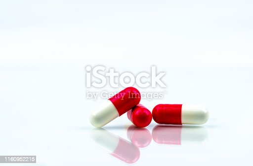 istock Red and white capsules pill isolated on white background with shadow and copy space. Antibiotics drug resistance. Antimicrobial capsule pills. Pharmaceutical industry. Global healthcare concept. 1160952215