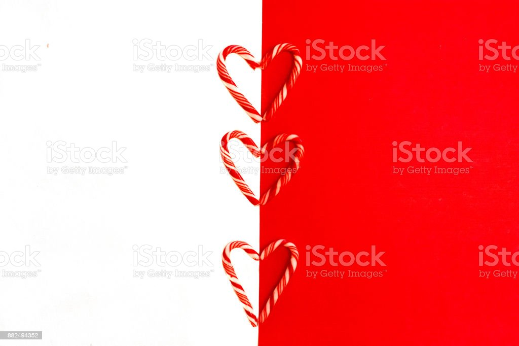 Red and white Christmas background with candy canes hearts stock photo