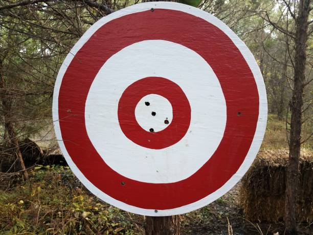 red and white circular target with holes in it stock photo