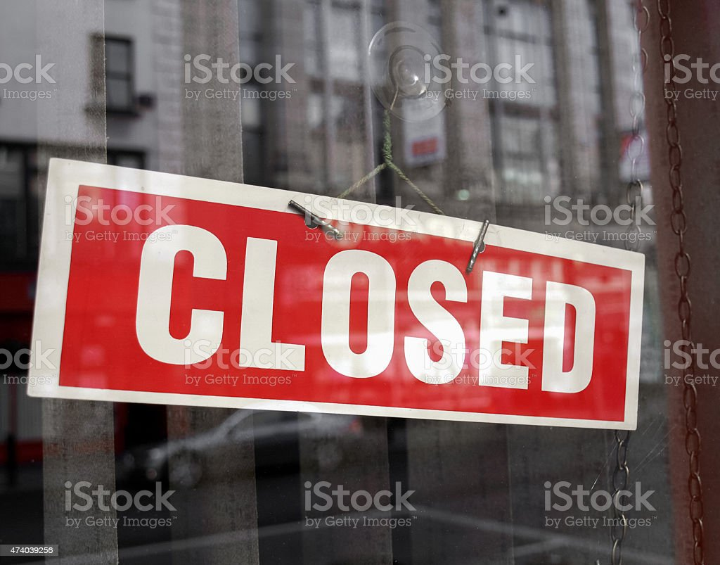 Red and white closed sign hanging in a shop window stock photo