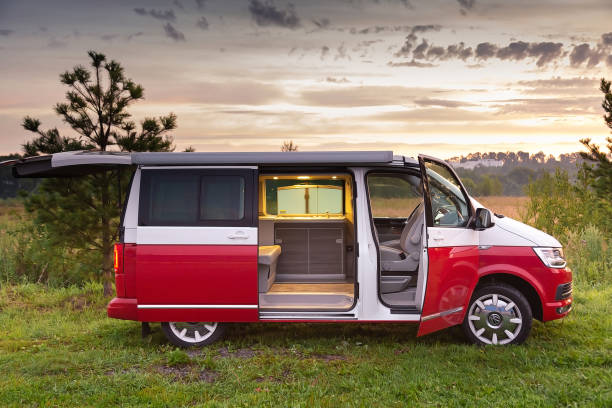 Red and white colored modern Volkswagen Multivan California Ocean (Transporter). Is Parked in the forest at sunrise. Side view and open doors stock photo