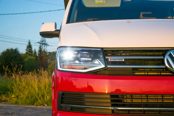 Red and white colored modern Volkswagen Multivan California Ocean (Transporter T6). Is parked on the country road. LED headlights closeup stock photo
