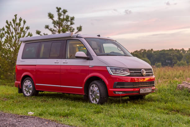 Red and white colored modern Volkswagen Multivan California Ocean (Transporter). Is Parked in the forest at sunrise. Front view stock photo