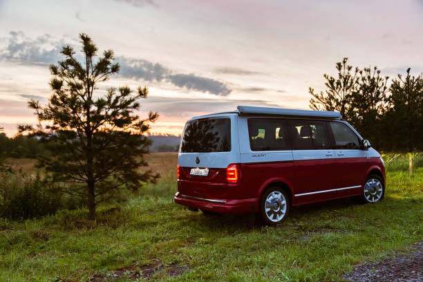 Red and white colored modern Volkswagen Multivan California Ocean (Transporter). Is Parked in the forest at sunrise. Back side view stock photo
