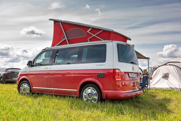 Red and white colored modern Volkswagen Multivan California Ocean (Transporter T6). Parked on the camping field. Back side left view stock photo