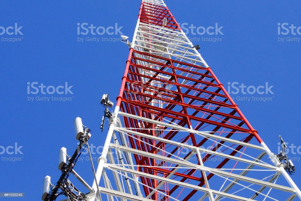 Red and White Communications Tower with Blue Sky Background Close UP stock photo