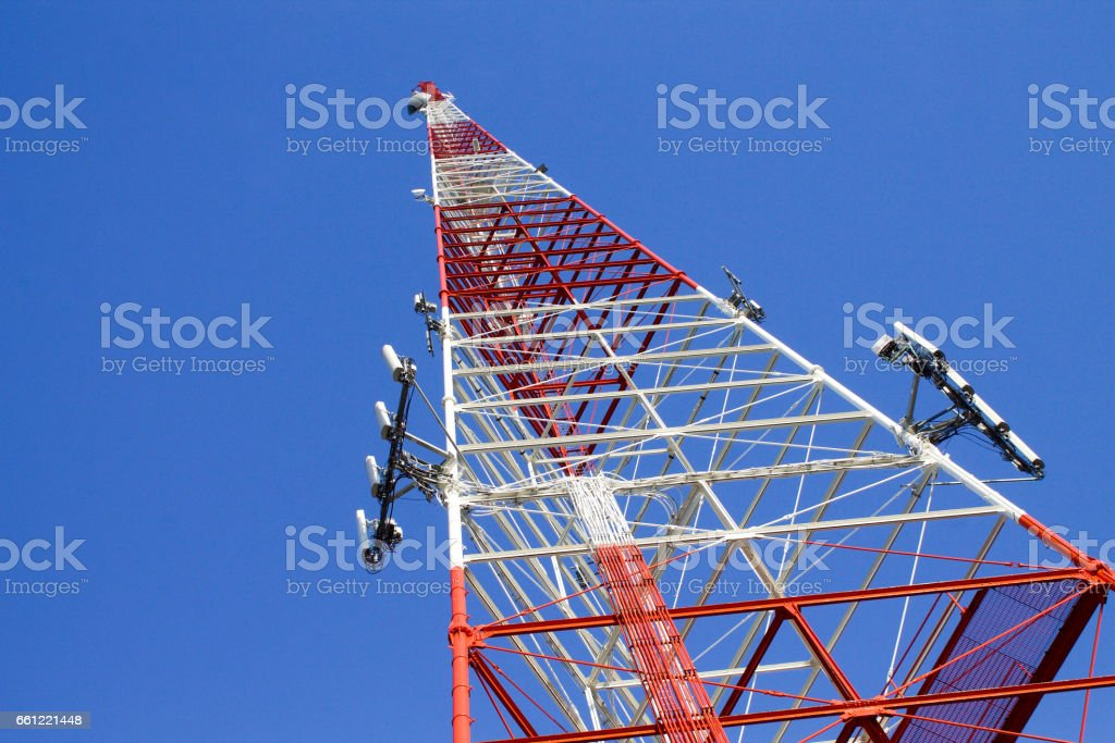 Red and White Communications Tower with Blue Sky Background stock photo