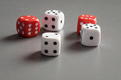 Two red and three white dice on a grey background.