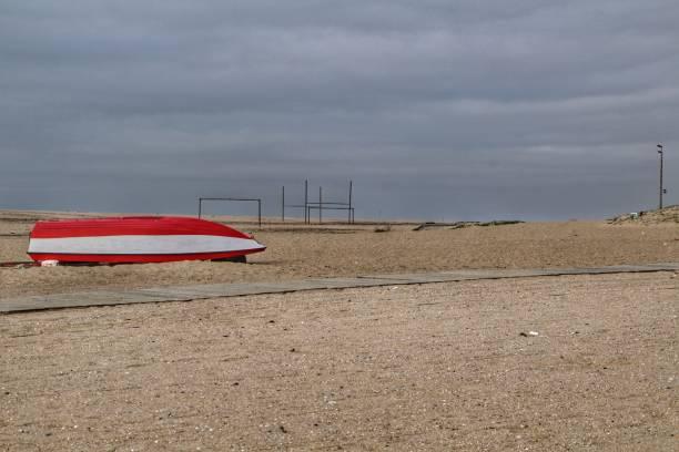 red and white fishing boat stranded on aguda beach - rain clouds porto portugal imagens e fotografias de stock