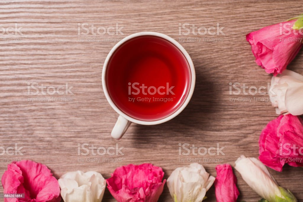 Red and white flowers and red tea in a white mug lying on the wooden background. Space for text and design. photo libre de droits