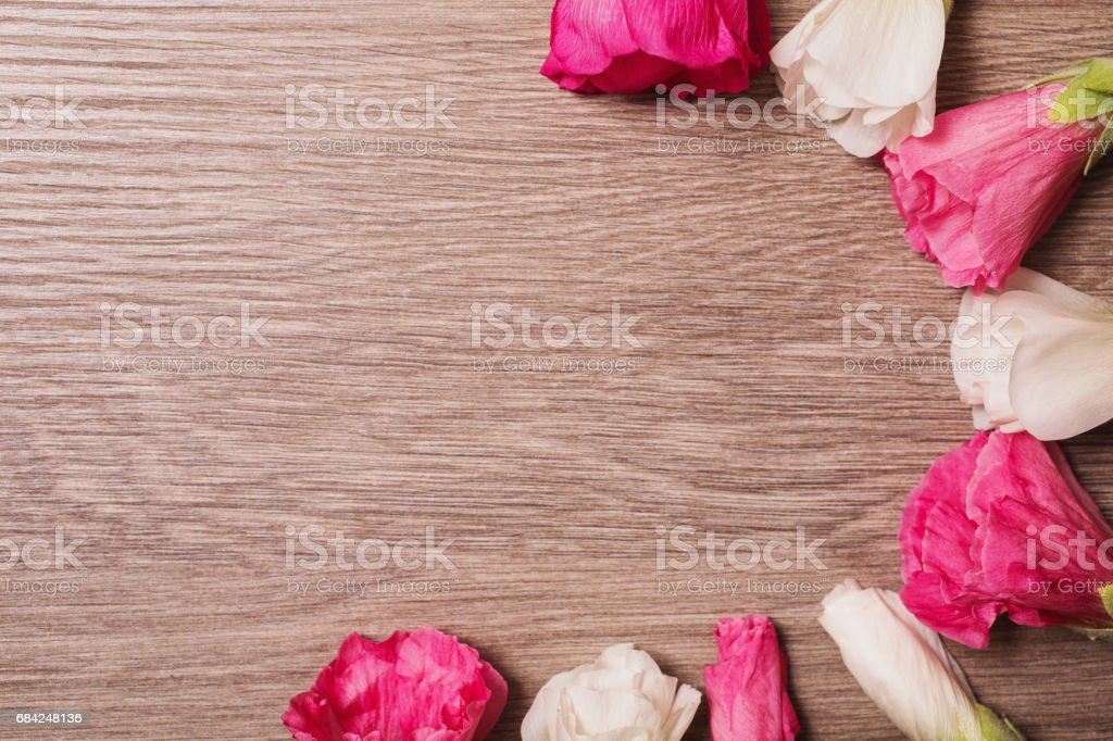 Red and white flowers lie on the wooden background. Space for text and design. Top view royalty-free stock photo
