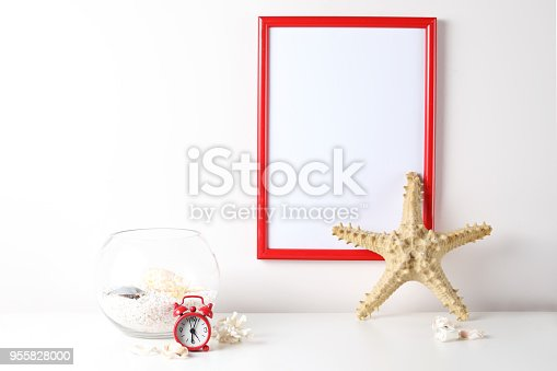 518847146istockphoto Red and white frame poster with plant in pot on table. 955828000