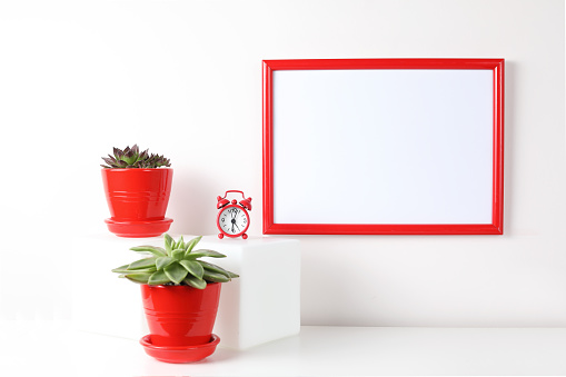 518847146 istock photo Red and white frame poster with plant in pot on table. 955828046