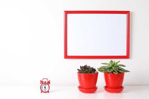 518847146 istock photo Red and white frame poster with plant in pot on table. 955828124