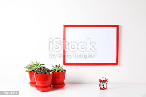 518847146istockphoto Red and white frame poster with plant in pot on table. 955828200
